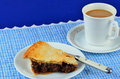 Coffee and pie slice of mincemeat with flaky golden brown crust cup of on very country style setting with blue gingham place mat Stock Photography