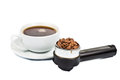 Coffee portafilter filled with coffee beans with a cup of freshly brewed espresso at the background Royalty Free Stock Image