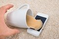 Coffee spilled on cellphone by misfortune from person s hand Stock Images