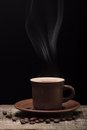 Coffee with Steam and Beans on Black Background Royalty Free Stock Photo