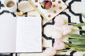 Coffee, strawberries, notebooks on Scandinavian rug. Pink Tulips and Gold Spoons. White black pattern and gold theme. Lifestyle co Royalty Free Stock Photo