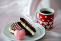 Coffee and sweets with a pink heart decorated mug of along chocolate cake whoopee pie Stock Photography