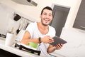 Coffee and tablet pc a young male sitting in the kitchen with a Royalty Free Stock Images