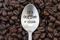 Coffee time beans and silver spoon with written it s o clock Stock Photography