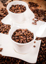 Coffee time two white cupps loaded with beans selective focus on the front cup Stock Image