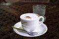 Coffee in white cup cappuccino and cold water Stock Photo