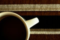 Coffee in white cup on striped cloth mat close up detail of a sitting a Royalty Free Stock Images