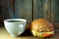 Coffee and wholegrain sandwich roll hot seeded cheese against a wooden background Stock Image