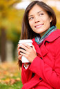 Coffee woman enjoying fall and coffee in autumn forest outside close up face portrait of asian wearing red coat beautiful Stock Images