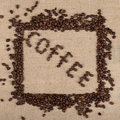 Coffee word made of beans with a frame of beans on a burlap background Royalty Free Stock Photography