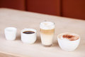 Coffees displayed in a row on wooden table variety of at cafe Stock Photo