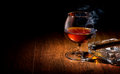 Cognac and cigar on ashtray on a wooden table Royalty Free Stock Images