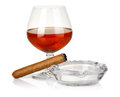 Cognac in glass with cigar and ashtray isolated Royalty Free Stock Photo