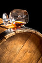 Cognac in glass on old vintage barrel closeup of Royalty Free Stock Photography