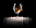 Cognac glass shrouded in a smoke on black background Stock Photography