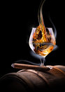 Cognac glass shrouded in a smoke on black background Stock Photos