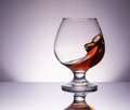 Cognac glass splashing in with reflection Royalty Free Stock Photos