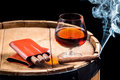 Cognac in a glass on wooden barrel closeup of Stock Image