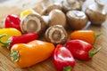 Cogumelos e pimentas coloridas que esperam para ser cortado. Fotos de Stock Royalty Free