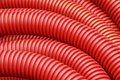 Coil of red plastic corrugated plumbing pipe Royalty Free Stock Photo