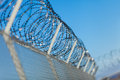 Coiled razor wire on top of a fence with its sharp steel barbs mesh perimeter ensuring safety and security preventing access Royalty Free Stock Photography