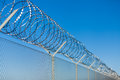 Coiled razor wire on top of a fence Royalty Free Stock Photo
