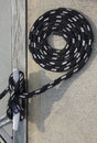 Coiled rope black at mooring Stock Image