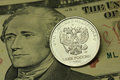 Coin in one Russian ruble against the backdrop of American ten dollar