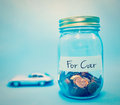 Coins in bottle on blue background concept save money for car Royalty Free Stock Photo