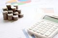 Coins, chart and a calculator as a symbol for exchange rates. Royalty Free Stock Photo