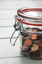 Coins in glass jar various a on a wooden table Stock Images