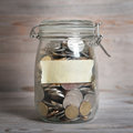 Coins in glass money jar with blank label financial concept vintage wooden background dramatic light Stock Photo