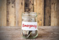 Coins in glass money jar with emergency label, financial concept Royalty Free Stock Photo