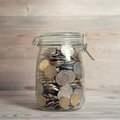 Coins in glass money jar financial concept vintage wooden background with dramatic light Stock Photos