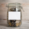 Coins in glass money jar with white blank label financial concept vintage wooden background dramatic light Stock Photography