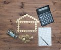 Coins in house shaped, calculator pen and notebook Royalty Free Stock Photo