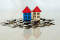 Coins and houses standing on it group of a small Royalty Free Stock Image