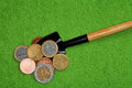 Coins and a shovel on a green background. Royalty Free Stock Photos