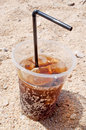 Cola with ice glass of cubes on the sandy beach Royalty Free Stock Images