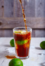 Cola that pour in glass with ice lime and rum limes around it proccess of making cuba libre cocktail or on wooden Stock Images