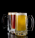 Cold beer three frozen mugs isolated on a black background with different style in each one Stock Photography