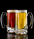 Cold beer two frozen mugs with a lager and a red ale on a dark background Royalty Free Stock Photography