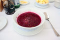 Cold beet soup on the table with pomegranate kernels served in white plate Royalty Free Stock Photos