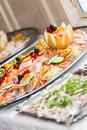 Cold buffet detail of food with fish and various fruits on silver plates Royalty Free Stock Image