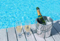 Cold champagne bottle in ice bucket and two glasses of champagne on the deck by the  bottle in bucket and two glasses of champagne Royalty Free Stock Photo