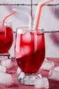 Cold cherry drink with ice cubes and cocktail tubes in glasses, on pink background Royalty Free Stock Photo
