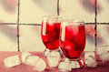 Cold cherry drink with ice cubes in glasses, on pink background Royalty Free Stock Photo