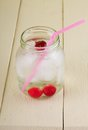 Cold cherry drink in jar with pink straw vertical photo of fresh from fruit which is inside ice cubes is too all is placed on Stock Photos