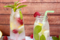 Cold cocktail with raspberries, lemon and mint. Wooden background