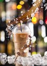 Cold coffee drink with ice beans and splash close up Stock Images